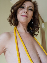 Busty goddess topless having fun with a yellow rope - Picture 7