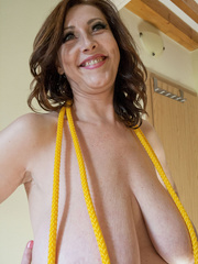 Busty goddess topless having fun with a yellow rope - Picture 8