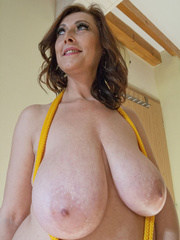 Busty goddess topless having fun with a yellow rope - Picture 9