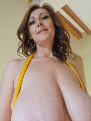Busty goddess topless having fun with a yellow rope - Picture 10