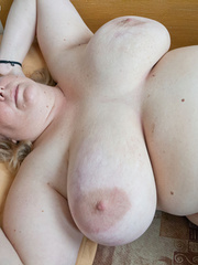 Blonde fatty playing with her giant titties laying on - Picture 1