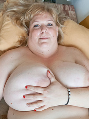 Blonde fatty playing with her giant titties laying on - Picture 3