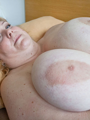 Blonde fatty playing with her giant titties laying on - Picture 4