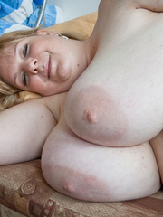 Blonde fatty playing with her giant titties laying on - Picture 9