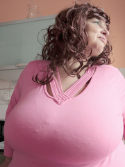 Curly brunette bbw in a pink pullover boasting with her - Picture 1