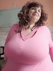 Curly brunette bbw in a pink pullover boasting with her - Picture 2