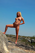 Blonde teen cutie posing absolutely nude in the rocks