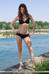 Young redhead takes off her bikini on the shore