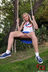 Cute teen in white top and blue skirt on swing…