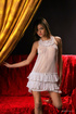 Slim young beauty in white nightdress shows sweet…