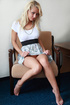 Slender blonde strips off printed dress and masturbates on a chair.