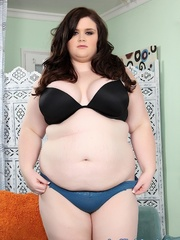Brunette in a black bra and blue panties disrobes and - Picture 1