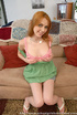 Redhead in a green dress and denim skirt does an old man on the couch.