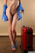 Tender minx in striped panties poses with her red luggage.