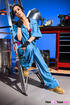 Chica in blue coveralls and red lingerie rubs her muff in the garage.