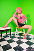 Asian babe in a pink fishnet top does a glass dildo on a chair.