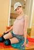 Chick in a knitted cap, see-through shirt and denim shorts strips and