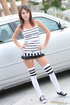 Playful red teen gal in a short striped dress showing off her tits outdoors