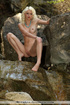 Blonde with a blue necklace posing naked by a waterfall.