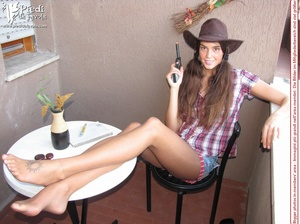 Little brunette pigtailed cowgirl wearing a hat, checked shirt and pantyhose looking dangerous with her gun - XXXonXXX - Pic 10