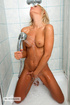Nude raunchy woman taking a shower and touching her twat.