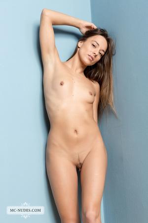 Wicked lady modeling her nude body against a blue wall. - XXXonXXX - Pic 1
