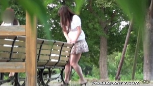 Cute Asian in sexy short skirt pressed on the streets hides to pee behind bench - XXXonXXX - Pic 12