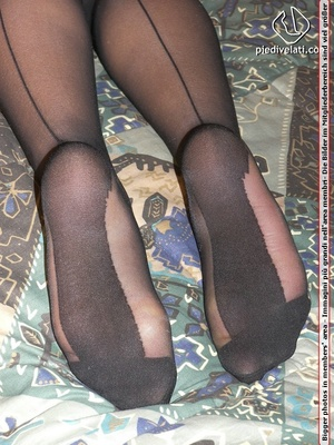Smiling damsel in cute short dress displays legs and feet in black hose on bed - XXXonXXX - Pic 8
