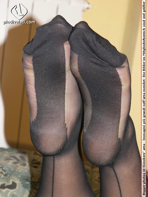 Smiling damsel in cute short dress displays legs and feet in black hose on bed - XXXonXXX - Pic 10