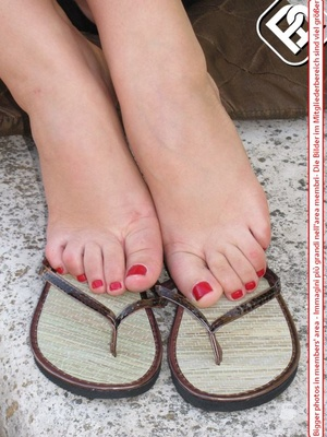 Knockout tart in flip flops displaying her yummy feet with red toe nails. - XXXonXXX - Pic 2