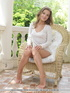 Beaver in a white dress exposes her wares on a wicker chair.