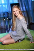 Floozy in a grey sweater poses naked on a green…