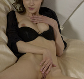 Fruity brunette in black dress and lingerie on bed loves apples and fingers
