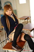 Damsel in a blue coat and black stockings face-sitting in the classroom.