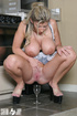 Dirty blonde mom in a maid's uniform collecting her love juice into a