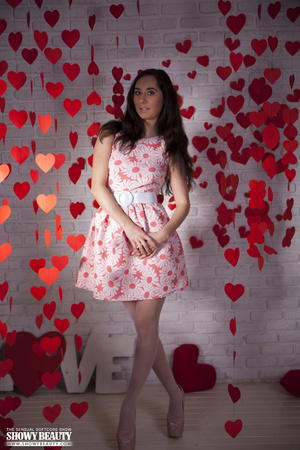 Desirable dish in a red dress with white daisies stripping in front of a brick wall. - XXXonXXX - Pic 2