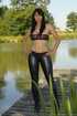 MILF on a dock by the lake is wearing tight black bottoms and a see-through