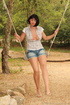 Girl in jean shorts on a makeshift swing shows off…