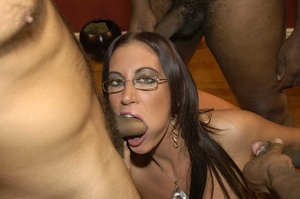 Smoking hot brunette wearing glasses and black fishnet stockings is surrounded by black monster dicks as she sucks them one at the time then she continues eating some while getting fucked in different positions by the others on a peach bed. - XXXonXXX - Pic 1
