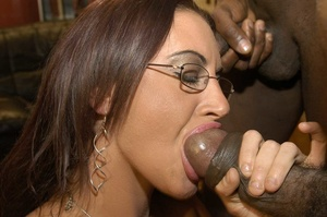 Smoking hot brunette wearing glasses and black fishnet stockings is surrounded by black monster dicks as she sucks them one at the time then she continues eating some while getting fucked in different positions by the others on a peach bed. - XXXonXXX - Pic 5