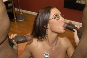 Smoking hot brunette wearing glasses and black fishnet stockings is surrounded by black monster dicks as she sucks them one at the time then she continues eating some while getting fucked in different positions by the others on a peach bed. - XXXonXXX - Pic 7