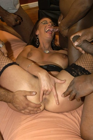 Smoking hot brunette wearing glasses and black fishnet stockings is surrounded by black monster dicks as she sucks them one at the time then she continues eating some while getting fucked in different positions by the others on a peach bed. - XXXonXXX - Pic 8