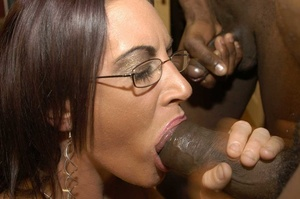 Smoking hot brunette wearing glasses and black fishnet stockings is surrounded by black monster dicks as she sucks them one at the time then she continues eating some while getting fucked in different positions by the others on a peach bed. - XXXonXXX - Pic 9