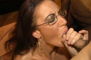 Smoking hot brunette wearing glasses and black fishnet stockings is surrounded by black monster dicks as she sucks them one at the time then she continues eating some while getting fucked in different positions by the others on a peach bed. - XXXonXXX - Pic 10