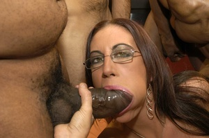 Smoking hot brunette wearing glasses and black fishnet stockings is surrounded by black monster dicks as she sucks them one at the time then she continues eating some while getting fucked in different positions by the others on a peach bed. - XXXonXXX - Pic 15