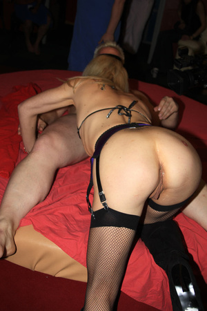 Blonde bombshell wearing violet and black lingerie bends over and fingers her ass crack before she lets multiple guys fuck and spray jizz on it on a red bed. - XXXonXXX - Pic 1