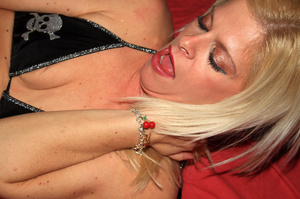 Blonde bombshell wearing violet and black lingerie bends over and fingers her ass crack before she lets multiple guys fuck and spray jizz on it on a red bed. - XXXonXXX - Pic 10