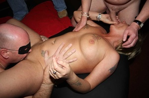 Tattooed blonde sucks a huge dick then takes off her flesh shirt and lets a group of guys fuck her while she sucks their cocks til she gets creamed on a black bed. - XXXonXXX - Pic 5
