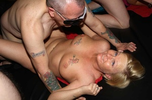 Tattooed blonde sucks a huge dick then takes off her flesh shirt and lets a group of guys fuck her while she sucks their cocks til she gets creamed on a black bed. - XXXonXXX - Pic 10