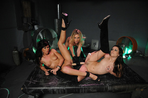 Blonde chick wearing black gloves and boots drills both ends of a long flesh dildo in the pussies of two hot lesbos wearing black high heels shoes and boots on a black bed before they lick each others pussies. - XXXonXXX - Pic 6